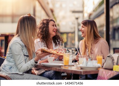 Three cheerful girls eating pizza in a outdoor restaurant. People,food,drink and lifestyle concept.