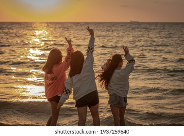 Three cheerful girls on the city beach waving to the setting sun. Israel Ashkelon October 18, 2020