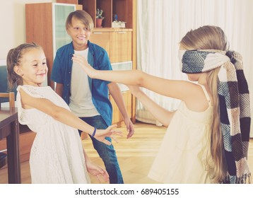 Three cheerful kids playing with blindfold in the living room