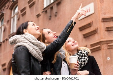 three cheerful modern female tourists while sight seeing in old town. one woman points up to a sight. other excited woman look up, too.