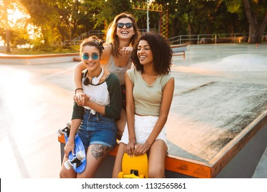 Three cheerful pretty young girls having fun with skateboards at the park