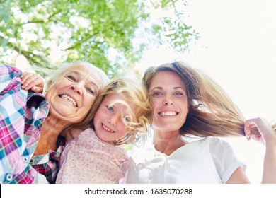 Three cheerful women in three generations as an extended family in the summer in the garden