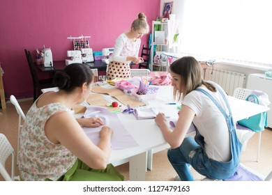 Three cheerful women working at fashion design studio. Fashion designers at work.