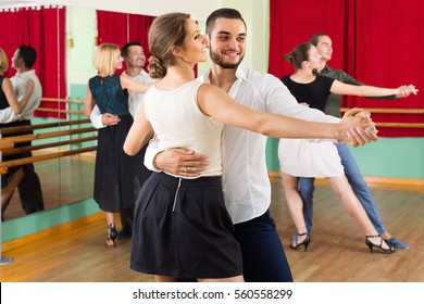 Three cheerful young couples dancing tango in the hall. Selective focus