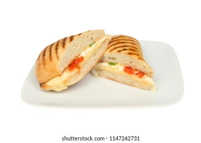Three cheese Panini, Cheddar, Mozzarella and Edam, with basil and tomato on a plate isolated against white