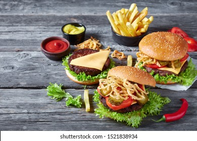 three Cheeseburgers with beef patties, cheddar cheese, crispy fried french onions, lettuce, sliced tomatoes, pickles on an old wooden table with mustard and ketchup, view from above, copy space left