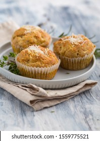 Three cheesy courgette muffins sprinkled with grated parmesan