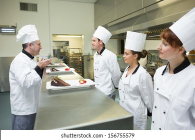 Three chefs presenting their dessert plates to the head chef in busy kitchen