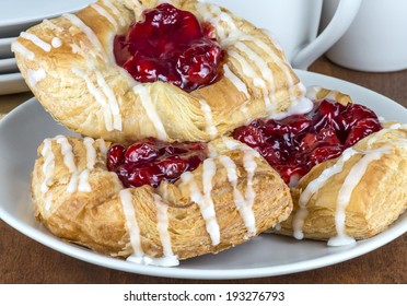 Three cherry Danish pastry on a plate