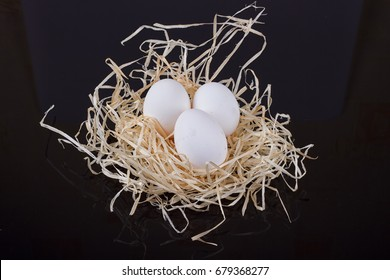 Three chicken eggs in the nest like On a black background