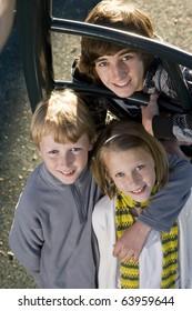 Three children (10 to 15 years) standing together on playground equipment