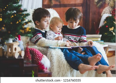 Three children, boy brothers, sitting in rocking chair in cozy living room with christmas decoration, reading a book, smiling