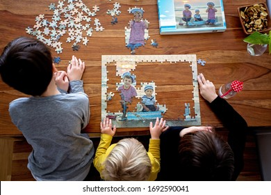 Three children, boys, assembling puzzle with their picture from the beach, playing at home together