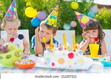 Three children celebrating birthday at outdoor party