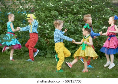Three children couples dance on grassy lawn outdoor.