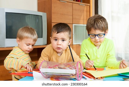 Three   children drawing with crayons at  table.