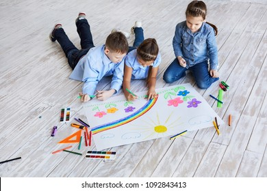 Three children drawing together on the floor