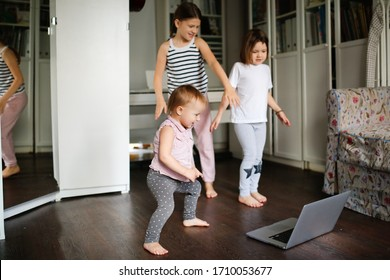 Three children are engaged in dancing, aerobics in video chat online with laptop, siblings dancing in front of laptop camera. kids remote sports and dancing, children's sports sections online.