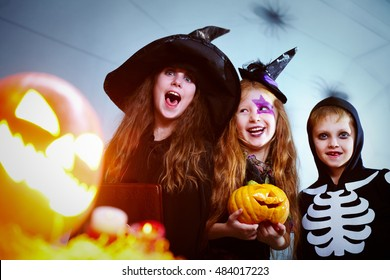 Three children in Halloween costumes, one holding a book and one  with a Halloween pumpkin screaming, looking at camera and smiling behind the flashing Jack O Lantern