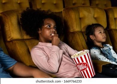 Three children having fun and enjoy watching movie in cinema