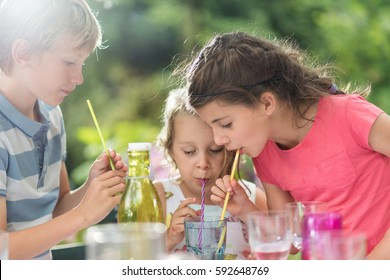 Three Children having a snack in the garden in summer. They drink with a straw in the same glass. Shot with flare