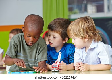 Three children in kindergarten playing with building blocks and cars