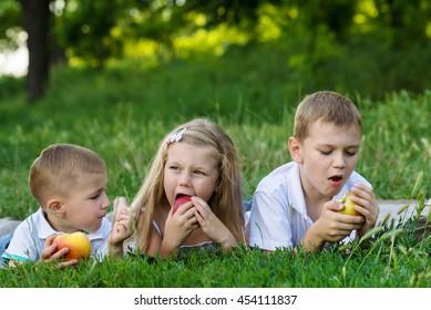 three children lay on the grass
