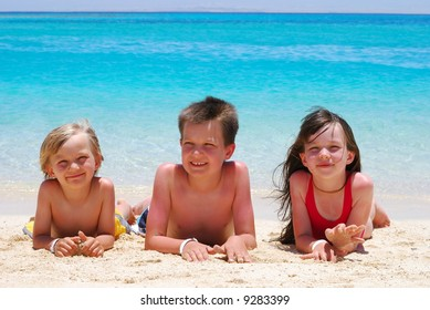 Three children laying in the sand on a tropical beach .