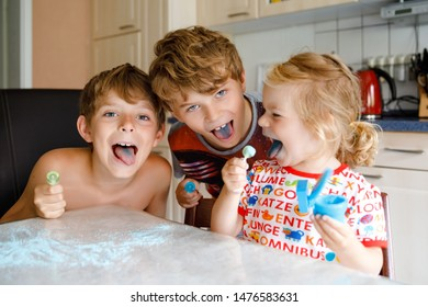 Three children licking lollypops and showing colored blue tongues. Funny siblings, two kids boys and cute toddler girl having fun together. Family of three, best friends