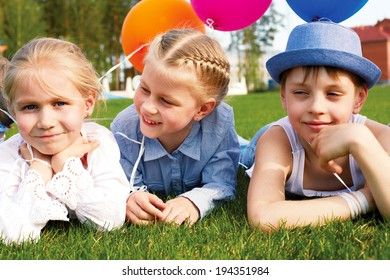 Three children lying on the grass with balloons