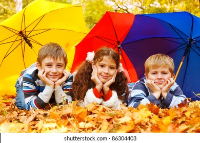 Three children lying under three colorful umbrellas