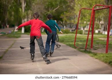 Three children on inline skates in park