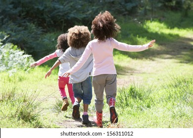 Three Children Playing In Woods Together