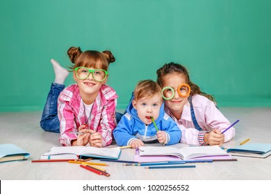 Three children read books and learn. The concept of childhood, learning, friendship, family, school, lifestyle.