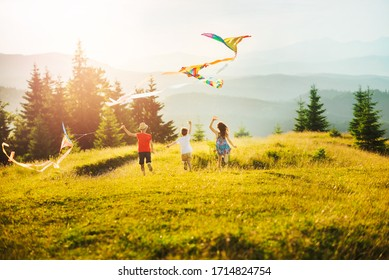 Three children running towards sun in mountains at sunset. Kids play with kites. Happy summer vacation and healthy lifestyle concept. Sunlit mountain ranges with coniferous trees.
