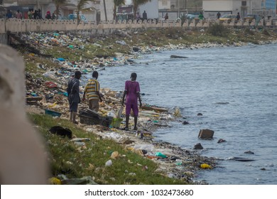 Three children in Sant Louis in Senegal dig through the trash on  the bank of the sea. Terrible pollution of water with waste washed ashore. Ecology problem in Africa.