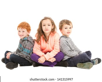 Three children sitting cross legged on floor waiting patiently. On white.