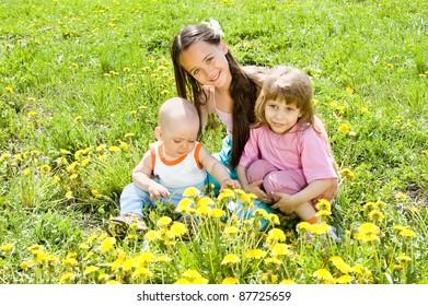 Three children sitting on the grass in the sun