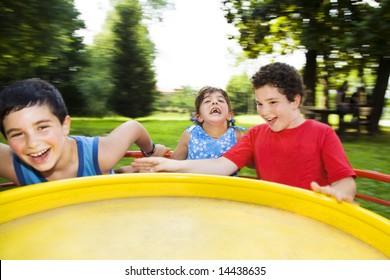 Three children spinning on merry go round