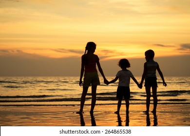 Three children standing on the beach at the sunset time