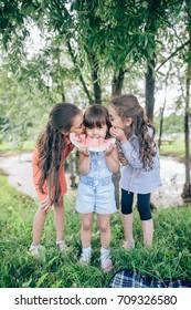 three children summer portrait. smiling children outdoor. children with watermelon. Three happy smiling child eating watermelon in park. Group of happy kids eating watermelon on grass in summer park
