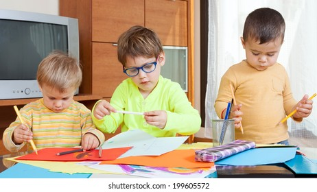 three children at  table with crayons and paper.