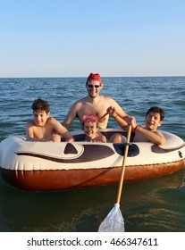 three children with their father on the dinghy in the sea in summer