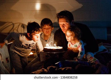 Three children, toddler girl and two school kids boys congratulating father to his birthday. Baby sister child, two brothers and dad with cake blowing candles. Happy healthy family portrait