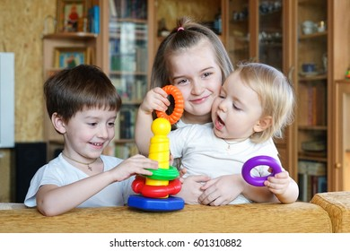 Three children together. The big brother helps the younger to assemble the toy pyramid