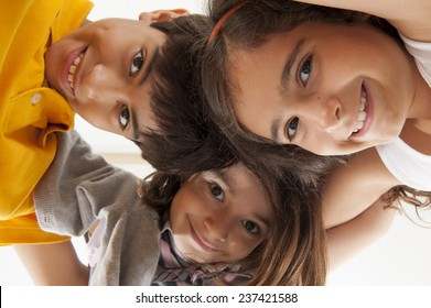 three children together and smiling .