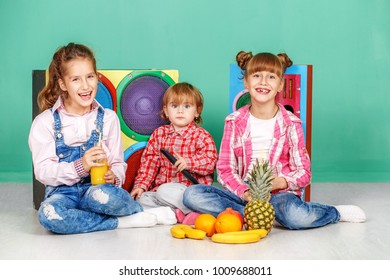 Three children watch tv and eat fruits. The concept of a healthy lifestyle, food, childhood, vitamins, vegetarianism.