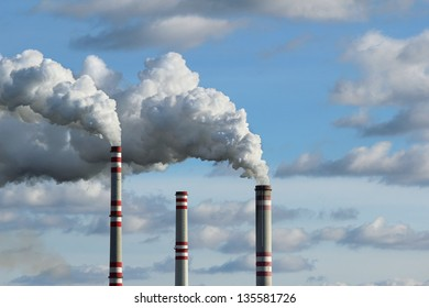 three chimney and white smoke polluted sky