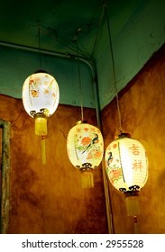 three chinese lanterns in the back of a shop
