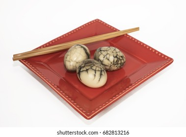 Three Chinese marbled tea eggs on a red plate with bamboo chopsticks against a white background.